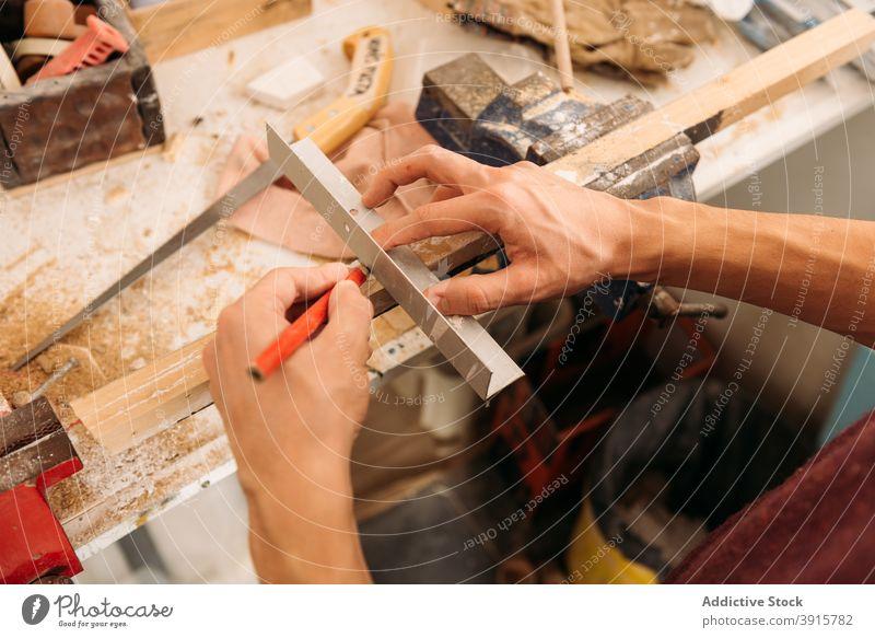 Crop woodworker using metal angle in workshop carpenter man carpentry plank male piece craftsman garage craftsmanship instrument tool equipment job pencil busy