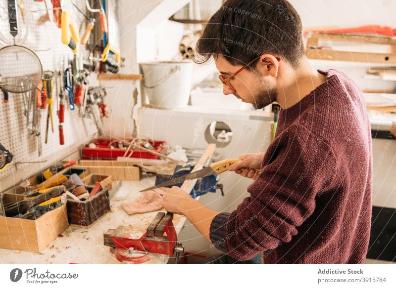 Focused male carpenter working with wood in workshop woodwork woodworker man cut plank saw carpentry sharp tool equipment job busy skill workbench concentrate