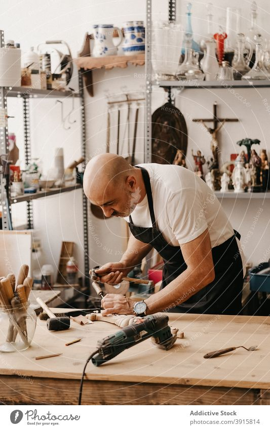 Artisan creating wooden detail in workshop carpenter woodwork chisel hammer create carve instrument professional tool man craft workplace timber carpentry