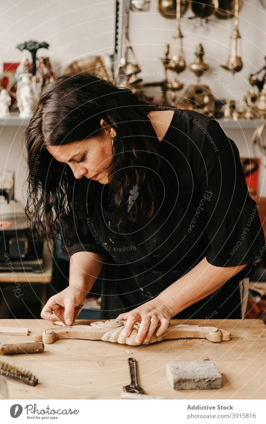 Craftswoman polishing wooden detail in workshop craftswoman carpenter woodwork carve create professional workplace woodworker timber carpentry handmade