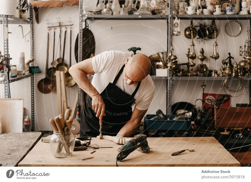 Craftsman carving wood in workshop carpenter carve woodwork chisel hammer create instrument professional tool wooden craft workplace woodworker timber carpentry