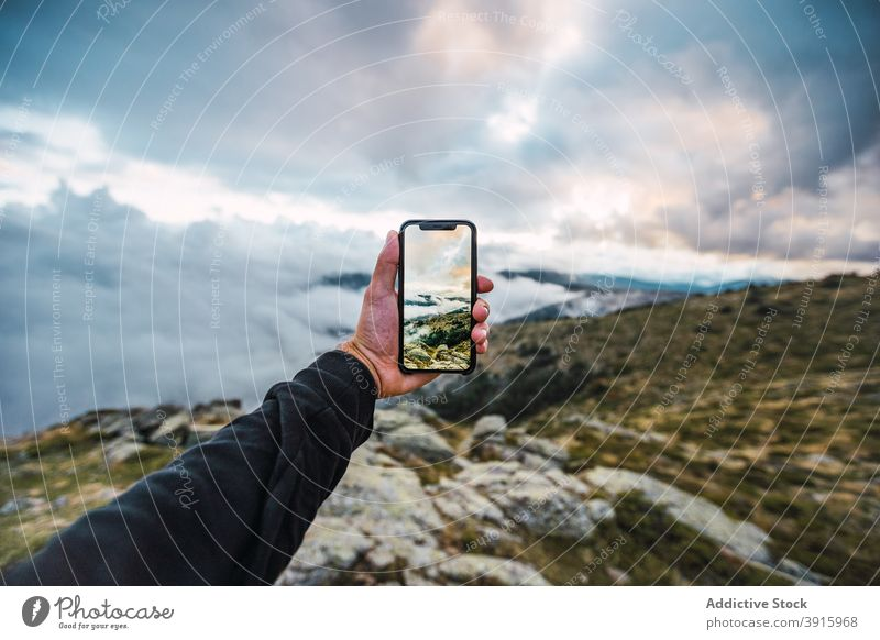 Crop traveler taking picture of highlands on smartphone take photo mountain incredible nature terrain rocky hiker male mobile adventure device gadget tourism