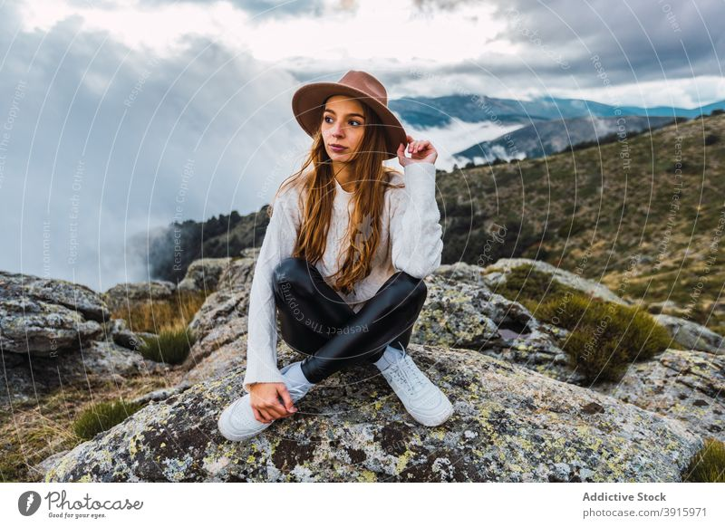 Woman in hat enjoying view of mountains woman observe viewpoint travel tourist highland admire explore female stone scenic sit nature traveler picturesque