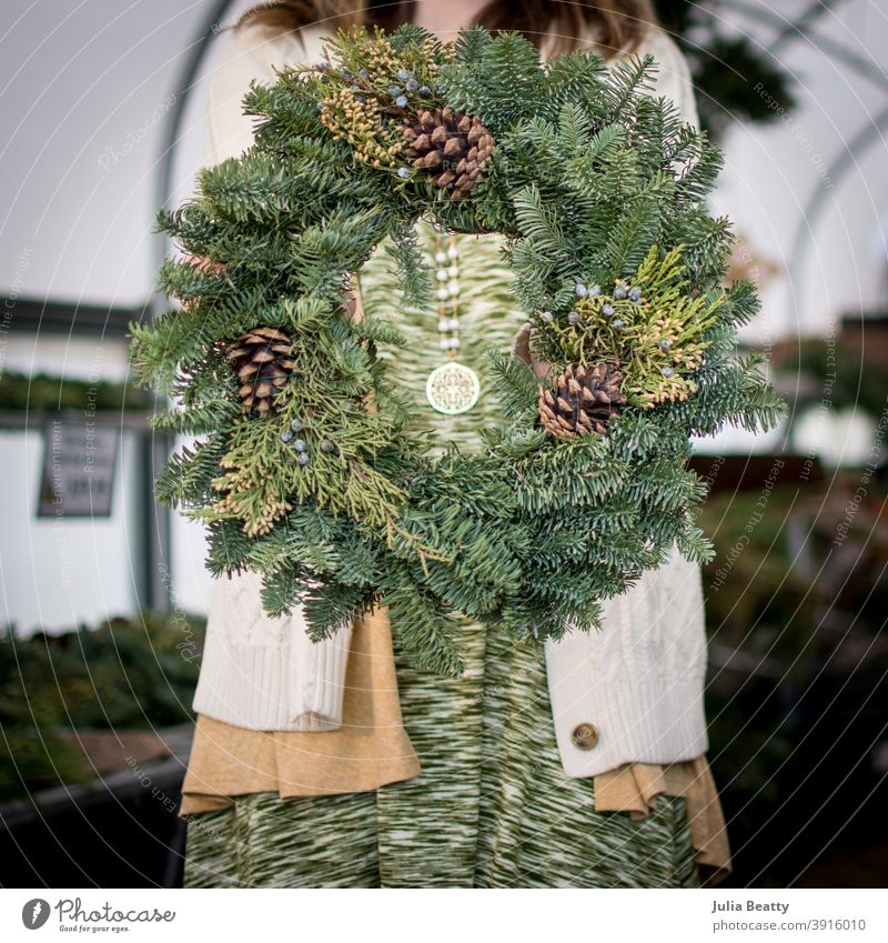 Woman holding Evergreen wreath with pine cones in front of body; inside of greenhouse christmas circle swag tree farm decoration decorate garland holiday x-mas