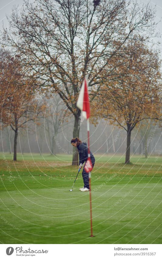 Middle-aged fit woman golfer putting for the hole on the green viewed from the flag concentrating for the next swing winter autumn windy misty middle-aged
