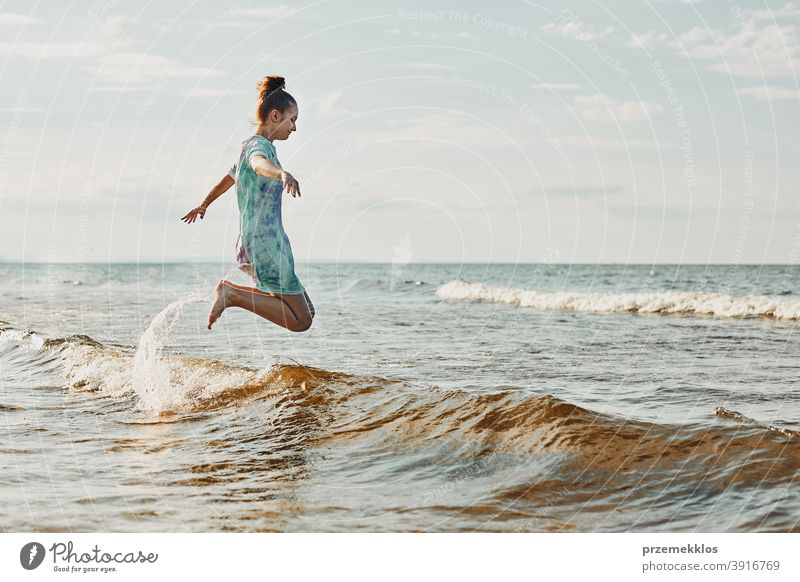 Girl enjoying sea jumping over waves spending a free time over sea on a beach during summer vacation excited positive sunset emotion carefree nature outdoors