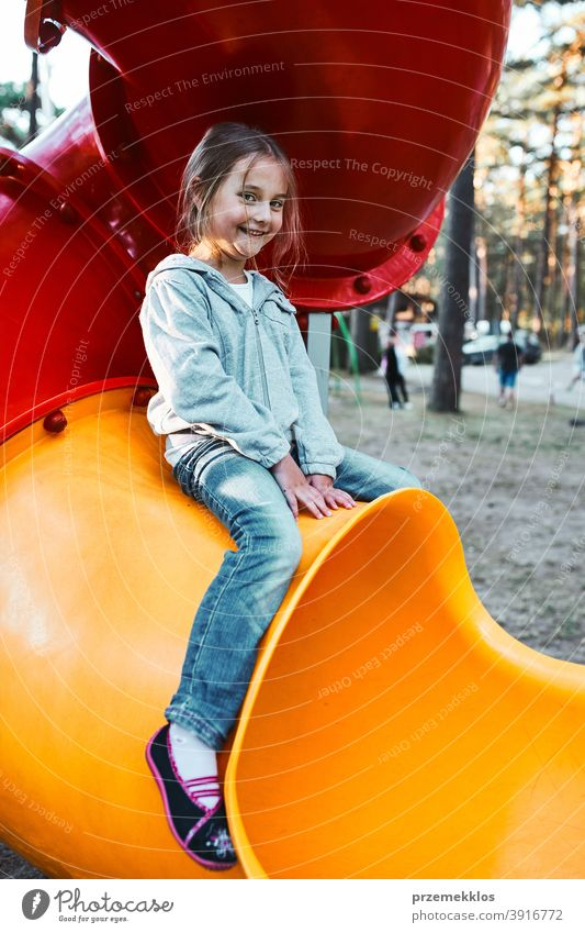 Little girl preschooler playing on a playground sitting on tube slide smiling and looking at camera positive joyful junior public place nursery climb outdoors