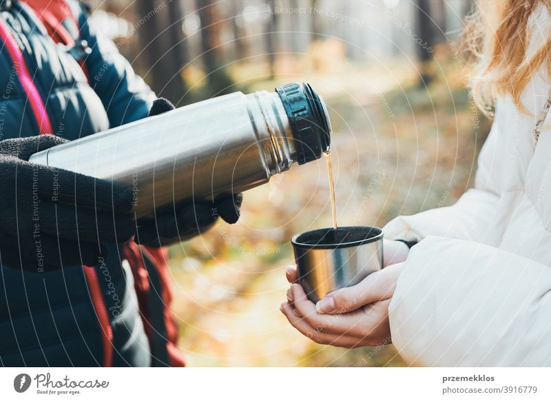 Women having break drinking hot tea during autumn trip on autumn cold day active activity adventure backpacker coffee cup destination enjoy exploration explore