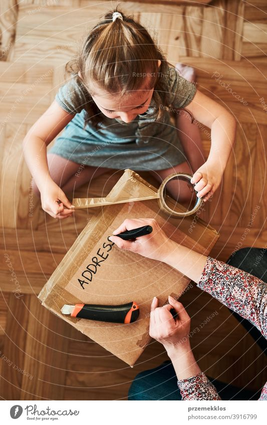 Woman writing an address on a cardboard box parcel preparing to send view floor gift unboxing tape girl daughter woman filler foam pack top open unpacking home