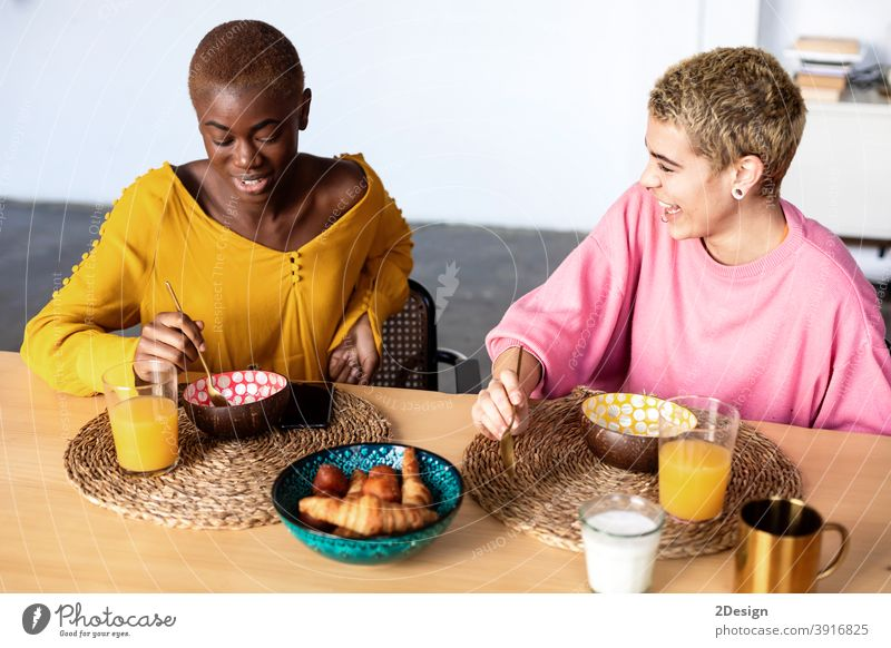 Two beautiful multiethnic girlfriends having breakfast together at home female sitting woman talking two people smiling togetherness discussing multiracial food