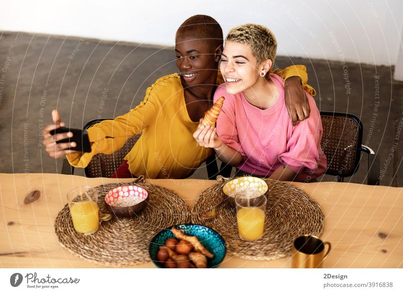 Beautiful young bestfriend females taking selfie using a smart phone and smiling while having a breakfast at home friendship domestic life together sitting