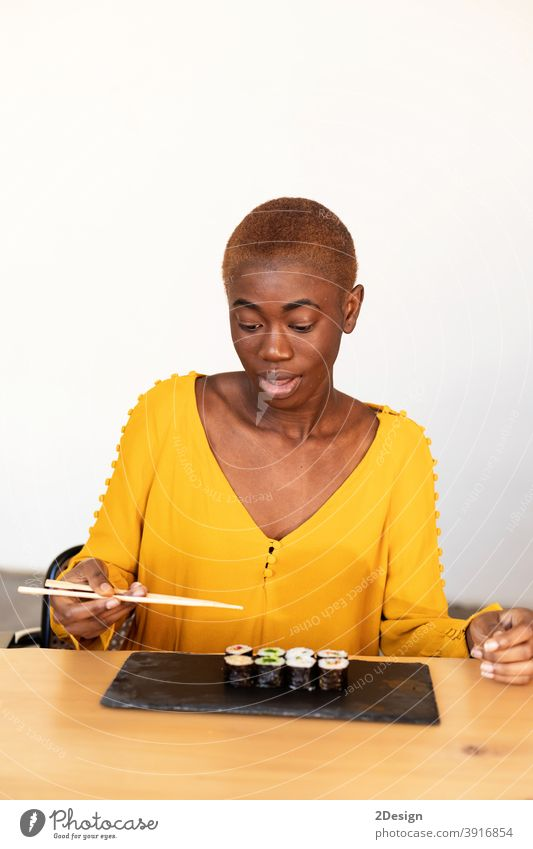 African american woman eating sushi using chopsticks at home with a confident expression on smart face thinking serious african holding japanese angry fish food