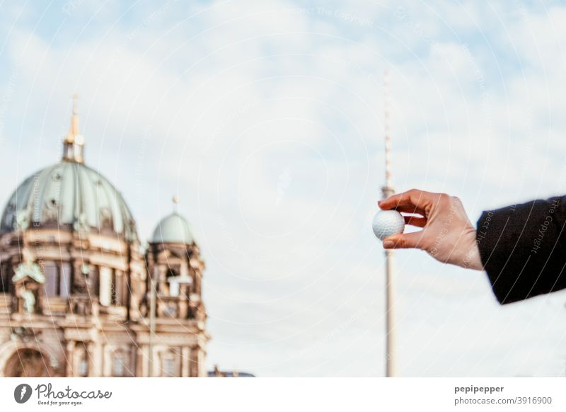 Golf ball held in front of Berlin television tower Berlin TV Tower Downtown Berlin Landmark Television tower Alexanderplatz Sky Berlin Cathedral