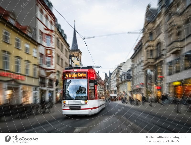 Moving tram in the old town Erfurt Tram Thuringia Town Old town anger houses Facades Church Church spire Driving Speed tempo Passenger traffic PUBLIC TRANSPORT