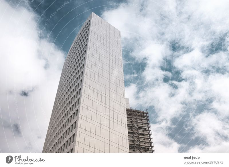 White office tower with scaffolding from frog perspective in front of blue sky Architecture High-rise Office building Facade Town outline Construction site