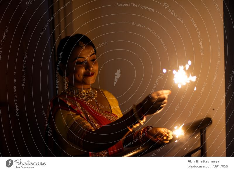 Young and beautiful Indian Bengali woman in Indian traditional dress is celebrating Diwali with fire crackers on a balcony in darkness. Indian lifestyle and Diwali celebration