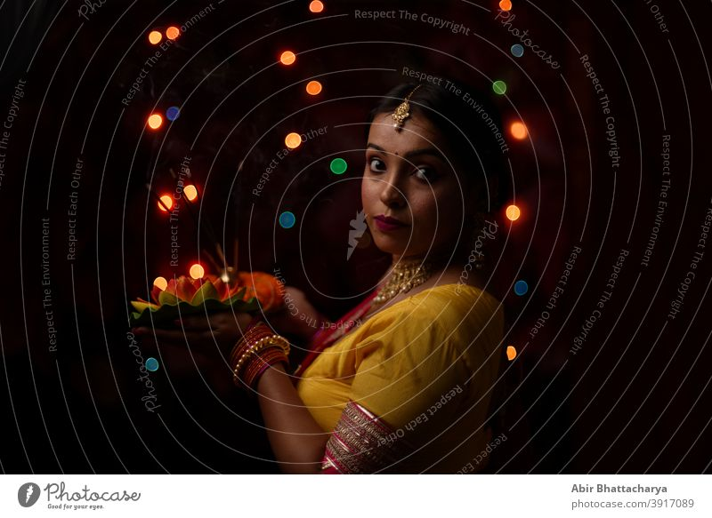 An young and beautiful Indian Bengali woman in Indian traditional dress is holding a Diwali diya/lamp in her hand in front of colorful bokeh lights. Indian lifestyle and Diwali celebration