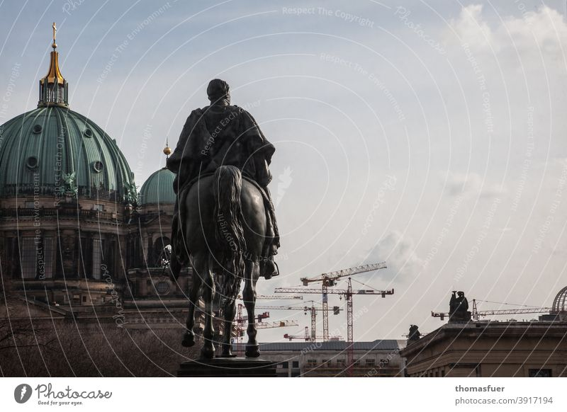 Equestrian statue in front of the cathedral and cranes in Berlin Dome old guard farsightedness outlook Sky Clouds Vantage point Contrast modern History of the