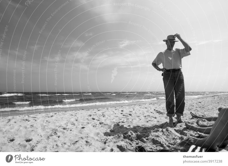 Man with hat on the beach and feet of some ladies Hat clad Pants T-shirt Beach Ocean Waves leg Wind Sun Clouds Shadow fresh from the summer wide vacation