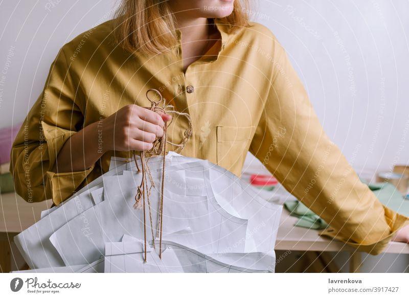 Female in yellow shirt holding paper dress patterns in her workshop tailor craft dressmaker fashion clothing occupation handmade faceless designer textile