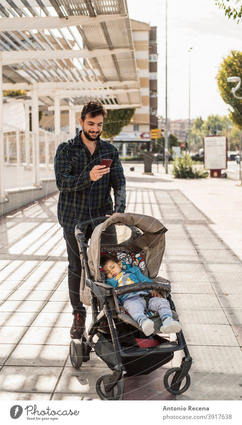 Bearded man with his sleeping baby on car looking phone father telephone walk baby car men male 40s adult attractive autumn beard bearded cool happy handsome