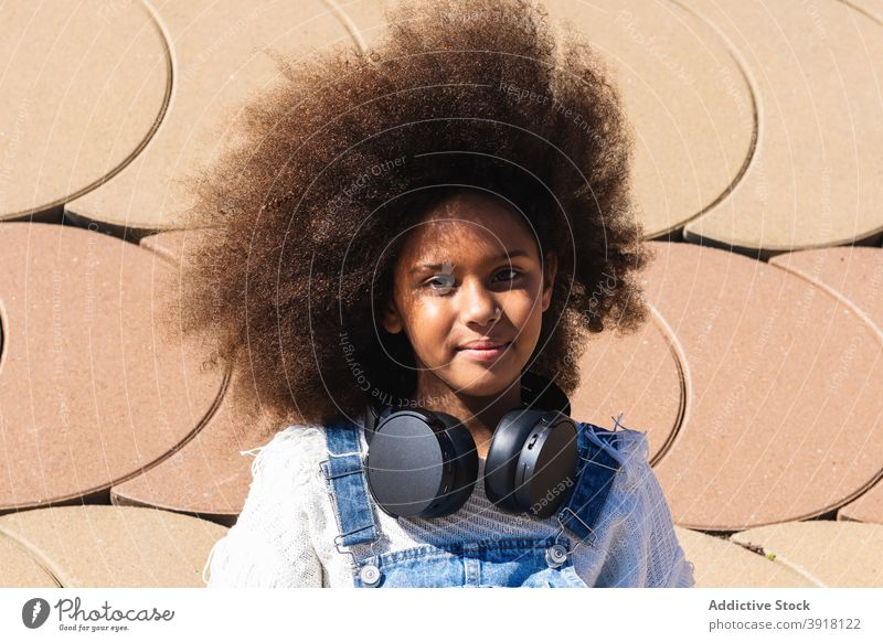 African American girl listening to music with headphones afro teen hipster wireless kid curly hair black african american ethnic female teenage device gadget
