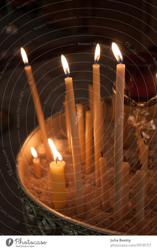 Lit beeswax candles in sand; Orthodox church lit light taper candles melt wick flame orthodox catholic prayer Candlelight Hope Church Belief Religion and faith
