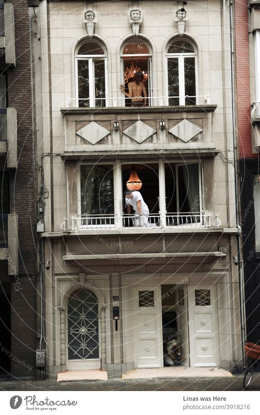 An accidental street photography shot of a random event in the same house. On the third floor, there is a topless woman, below you can see some repairmen doing their work. This action is located somewhere in the streets of Antwerp, Belgium.