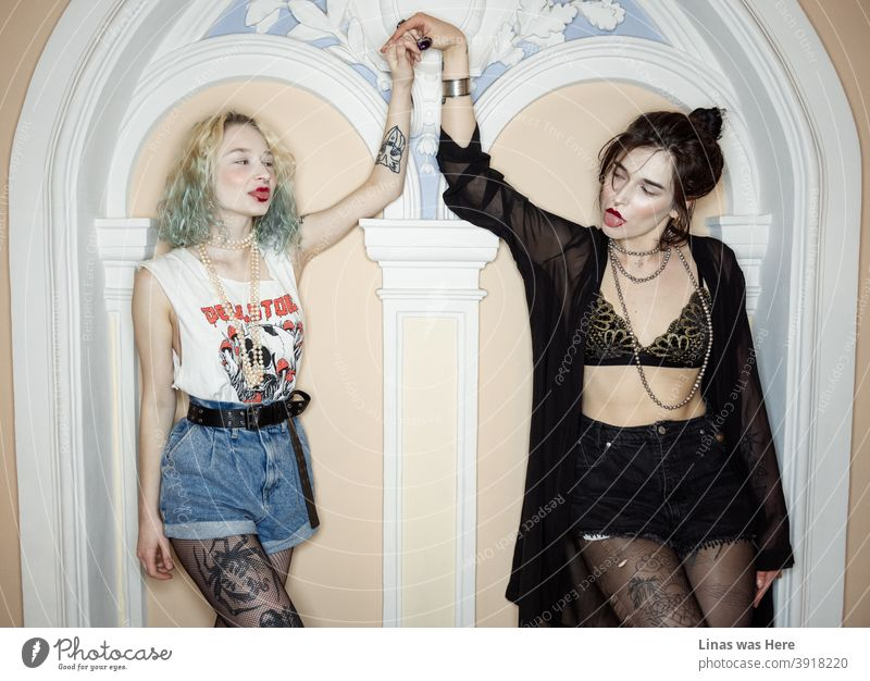 Young blood and positive energy. Two wild girls with tattoos are holding hands inside a fancy mansion with a classy interior. Girls just want to have fun!
