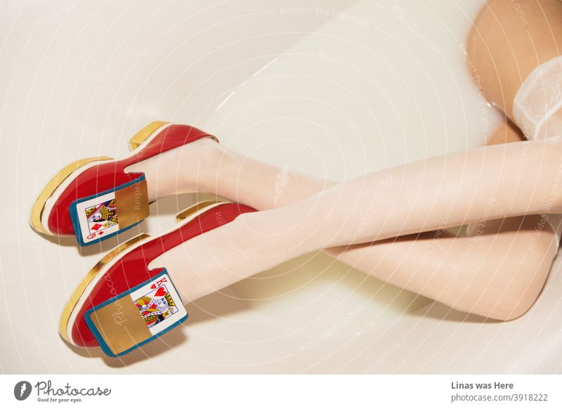 These shoes were definitely not made for walking in the fields. Why not try milky bath instead. A photo of stylish, golden, red, avant-garde women shoes in a milk bath. Oh, and you can see long and gorgeous legs in it as well.