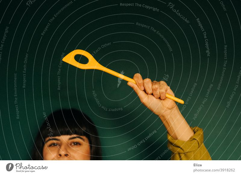 A woman holds up a yellow wooden spoon Wooden spoon Yellow boil Woman cutlery Kitchen Swing wield the cooking spoon Tall person Human being motivated Green