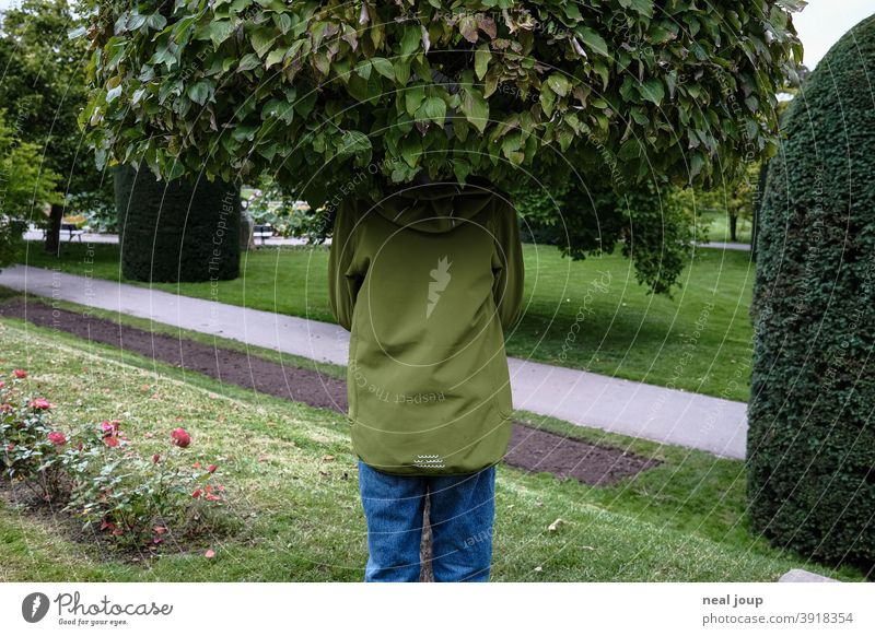 Child hides in tree top Nature Hiding place Hide Treetop leaves Whimsical surreal Head Green Camouflage fun original Exterior shot Freak Humor tone-in-tone