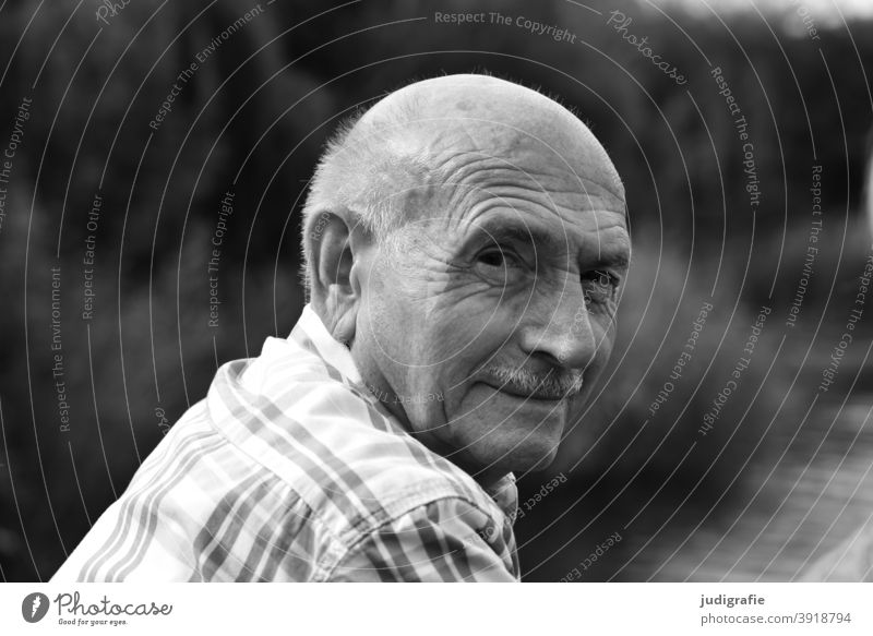 Senior looks friendly over his shoulder into the camera Senior citizen Man portrait Male senior Human being Grandfather Adults Masculine Exterior shot