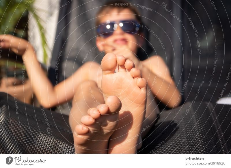 Kid with sunglasses lying on a deck chair Summer Sun feet Legs Toes Child Lie Relaxation holidays Barefoot Vacation & Travel Feet Exterior shot Sunglasses