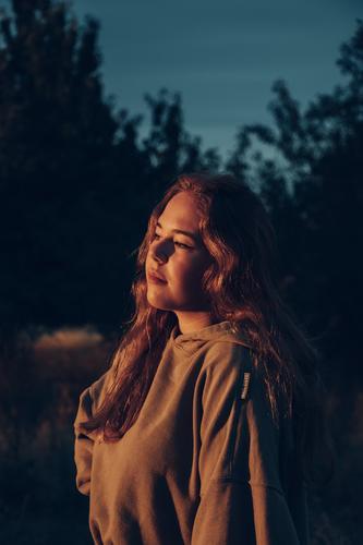 Portrait of a woman in sunset Portrait photograph portrait Sunset Orange orange tones afternoon face long hair Face of a woman eyes hoodie