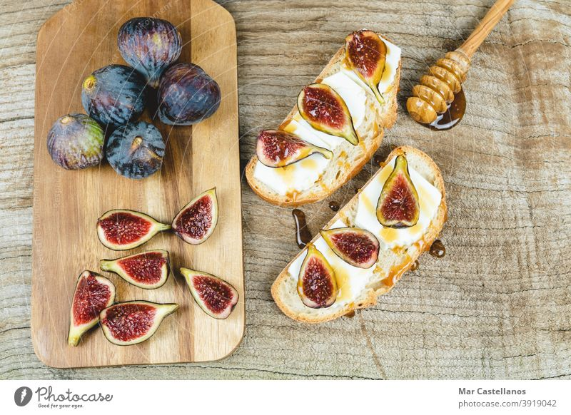 Figs cut on toast with cheese. figs bread breakfast snack ripe fruit whole kitchen table wooden bottom copy space top view purple tasty piece delicious sweet