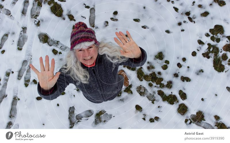 Drone shot of woman in snow waving upwards Woman Winter Snow Wave Laughter Aerial photograph droning UAV view drone Funny fun pleased laughing Senior citizen