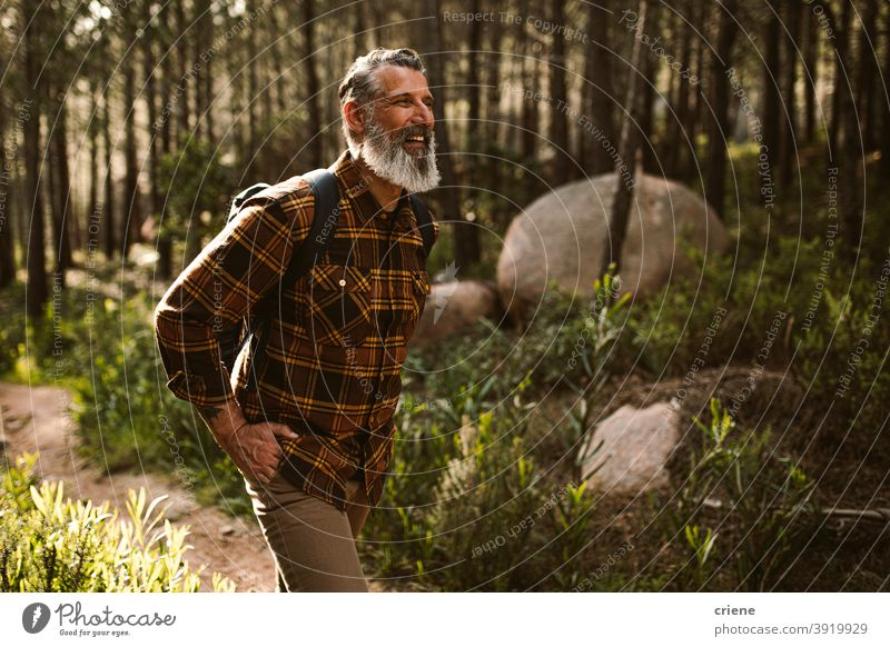 Happy Senior man smiling on hike in forest hiking sunny senior retirement adventure fun happy wellbeing walking lifestyle leisure laughing positive hipster