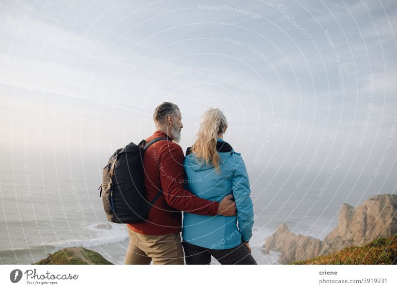 senior couple looking at the sea together on vacation woman people family love happy travel nature sky outdoors hiking mountain tourist walking holiday water