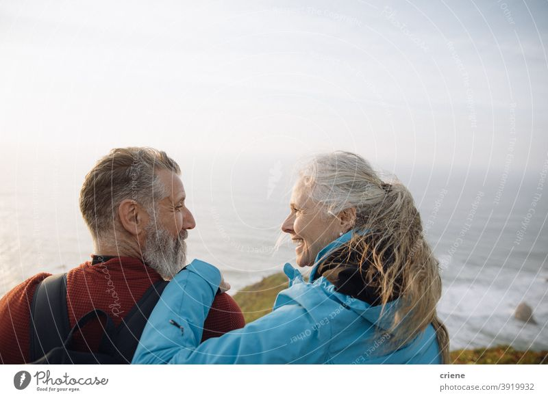 caucasian senior couple sitting on cliff enjoying sunset together looking at each other woman happy old elderly love smiling people family mature retirement