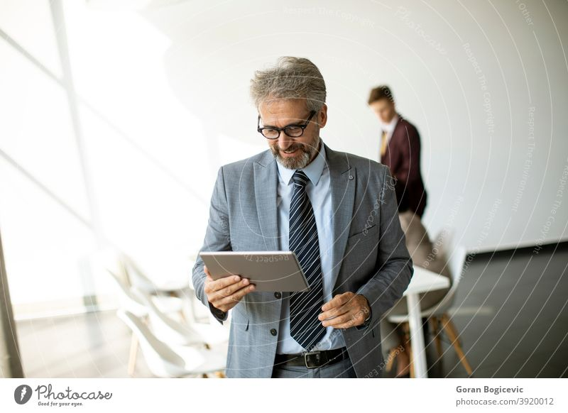 Handsome mature businessman using his tablet in the office adult age alone attractive businessmen businesspeople career caucasian confident contemporary