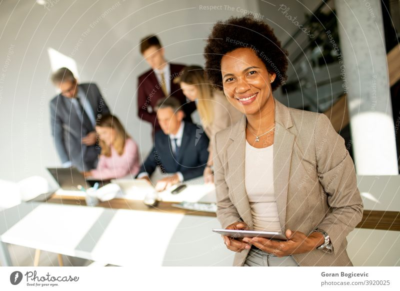 African American businesswoman standing and using digital tablet in a modern office adult african afro american beautiful black cheerful communication confident