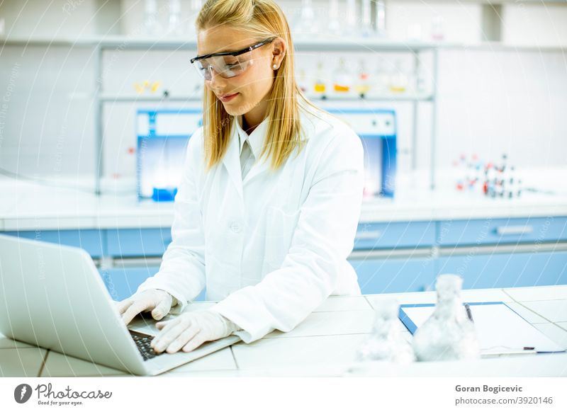 Female researcher in white lab coat and protective goggles using laptop while working in the laboratory analyzing background bio chemical chemist clinic