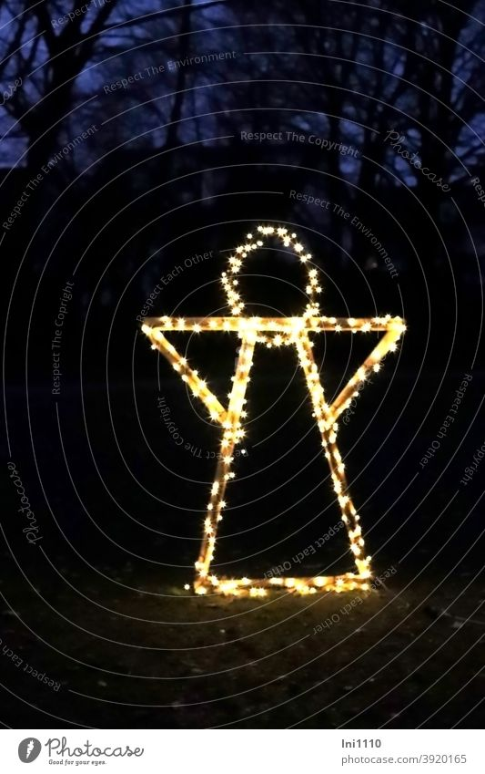 Angel decorated with a chain of lights stands illuminated in the park Christmas & Advent Christmas decoration Framework Wood Metal Fairy lights Illuminated