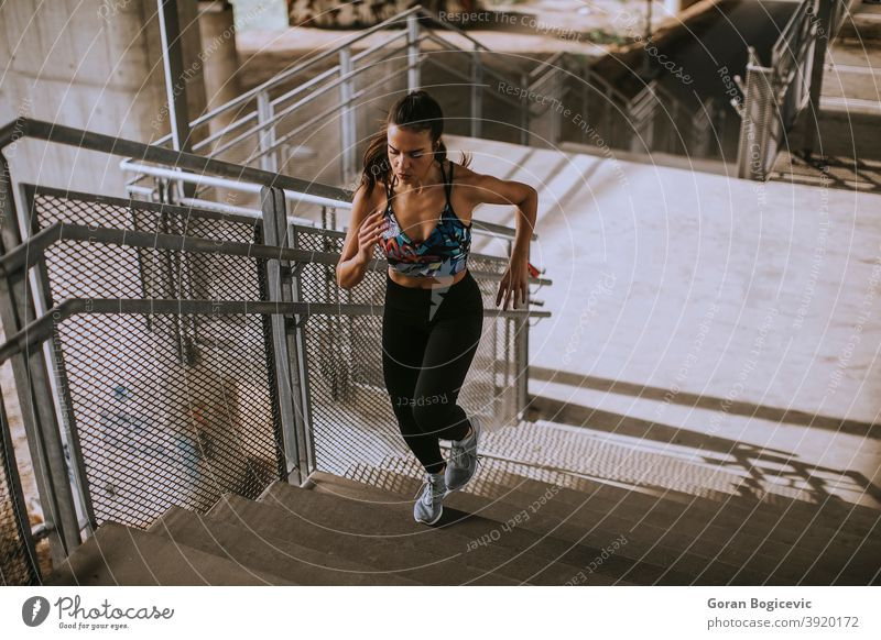 Young woman running in the urban environment stairs exercise training fitness female runner athlete workout city young lifestyle healthy person activity one