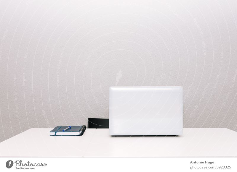 White table and chair. Laptop and agenda. Teleworking concept. Grey background. desk laptop white teleworking grey business office computer document modern