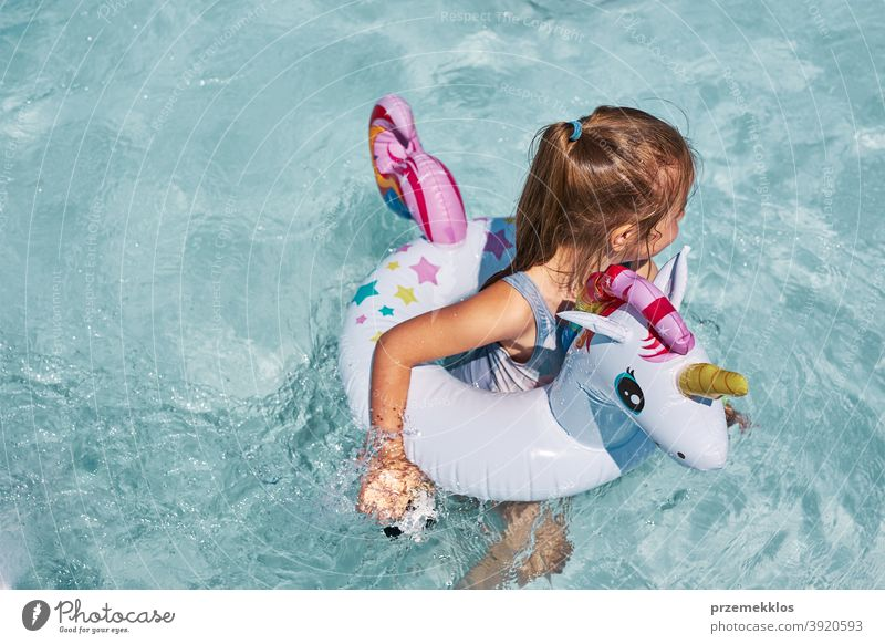 Little girl playing in a swimming pool with inflatable ring toy in the shape of unicorn authentic backyard childhood family fun happiness happy joy kid