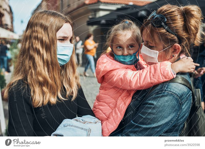 Family mother and her daughters standing in a street downtown wearing the face masks to avoid virus infection call care caucasian chat contagious corona