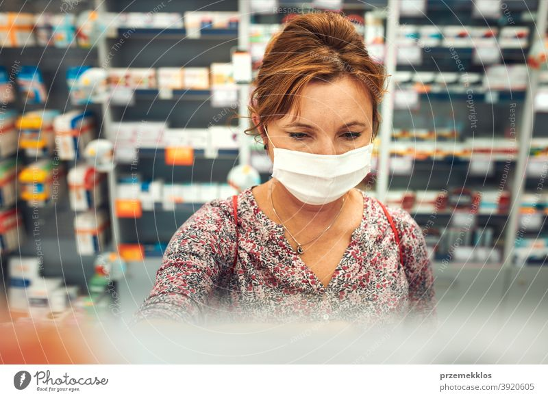 Woman shopping at pharmacy, buying medicines, wearing face mask during pandemic coronavirus outbreak woman chemist covid-19 cover standing town female care