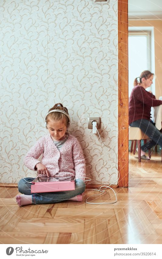 Little girl preschooler learning online solving puzzles playing educational games on tablet at home attention bed bedroom caucasian child childhood computer